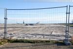 Vor dem Bauzaun der JadeWeserPort-Baustelle in Wilhelmshaven